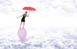 Girl with a red umbrella walking barefoot on a balloon flying in Royalty Free Stock Image
