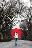 Girl with red umbrella walking in park in fall Royalty Free Stock Photos