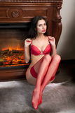 Girl in red underwear sits near fireplace Royalty Free Stock Image