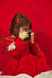 A girl in red using a vintage photo camera Stock Photos