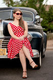 Girl in red with vintage car. Cute girl sitting on bumper of vintage car stock photo