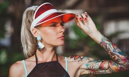 The girl in the red visor looking into the distance. Arms tattooed. Modern beach-ready look. The girl in the red visor looking into the distance. Arms tattooed Royalty Free Stock Image