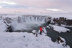 Girl in red warm shirt standing at Godafoss,Famous travel destinations waterfall in winter in North Iceland. stock photography