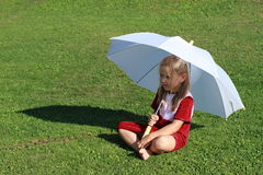 Girl in red with white umbrella. Barefoot little girl in red dress sitting with a white umbrella royalty free stock photography