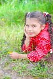 Girl in red windbreaker lying on the grass Royalty Free Stock Images