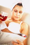Girl with red wine. And newspaper close up stock photo