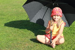 Girl in red and yellow dress with black umbrella. Barefoot little girl in red and yellow dress sitting with a black umbrella stock images