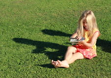 Girl in red and yellow dress sitting with money. Barefoot girl in a red and yellow dress sitting on the grass watching lots of money royalty free stock images