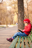 Girl reding tablet pc in the park. Computer genera Stock Photos