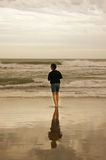 Girl with reflection in the water. Girl standing at edge of water at a beach of Mar del Plta, Argentina with reflection of her Stock Photos