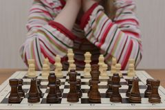 The girl reflects on the first chess move stock photography