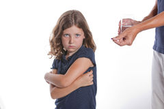 Girl Refuses Medicine. A adorable little girl with a sad face turns away from her parent, unwilling to take the medicine pill being offered Stock Photos