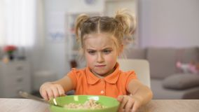 Girl refusing eat breakfast oatmeal, pushing bowl away, healthy child nutrition. Stock footage stock footage