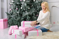 The girl rejoices to a large number of gifts on Christmas eve. Blonde girl hugging a big handful of gifts sitting on the floor near the big Christmas tree Royalty Free Stock Photo