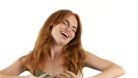 Girl rejoices in victory. White background. Redhaired girl with freckles rejoices in victory, shows thumbs up, she is happy to triumph. White background stock footage