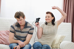 Girl rejoicing that beat boyfriend in console Stock Photography