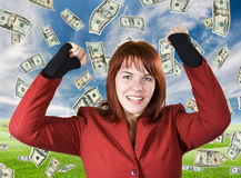 Girl rejoicing with dollars falling. Cute girl with red hair dressed in a red business dress with her arms raised smiling and rejoicing for a win. Dollars stock photos