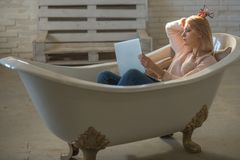 Girl relax in bathtub with laptop keep blog. Woman work on computer in home bath. Agile business and communication. Buy. Online and digital marketing Royalty Free Stock Images