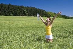 Girl relaxed. A beautiful woman feels happy on the field Royalty Free Stock Images