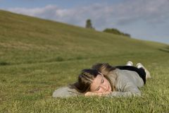 A girl is relaxed on the grass and has his eyes closed. A girl is lying relaxed on the grass and has his eyes closed royalty free stock photography