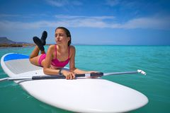 Girl relaxed lying on paddle surf board SUP royalty free stock photo