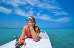 Girl relaxed lying on paddle surf board SUP royalty free stock images