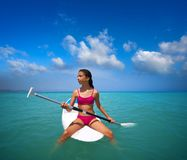 Girl relaxed sitting on paddle surf board SUP. In summer stock image