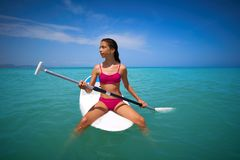 Girl relaxed sitting on paddle surf board SUP. In summer royalty free stock image