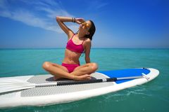 Girl relaxed sitting on paddle surf board SUP royalty free stock image