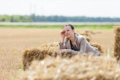 Girl relaxes on a haystack Royalty Free Stock Photos