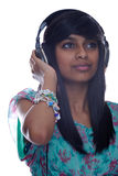 Girl relaxes to music. A teen indian girl listening to music on headphones Stock Images
