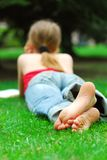 Girl relaxing. Young girl relaxing with a book on green grass in a summer park Stock Image