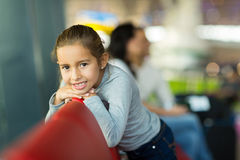 Girl relaxing airport. Pretty little girl relaxing at airport with parents in background Stock Photo