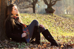 Girl relaxing in autumn light at the park Royalty Free Stock Image