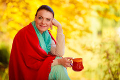 Girl relaxing in the autumn park enjoying hot drink Royalty Free Stock Images