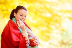 Girl relaxing in the autumn park enjoying hot drink Stock Photos