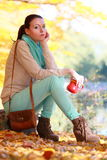 Girl relaxing in the autumn park enjoying hot drink Stock Photography