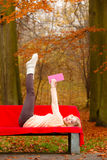 Girl relaxing in autumn park reading book Stock Photography
