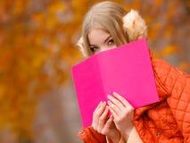 Girl relaxing in autumn park reading book Stock Photos