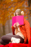 Girl relaxing in autumn park reading book Stock Image