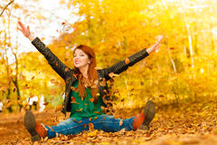 Girl relaxing in autumn park throwing leaves up in the air. Royalty Free Stock Photography
