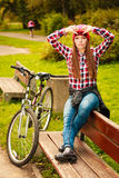 Girl relaxing in autumnal park with bicycle. Stock Photo