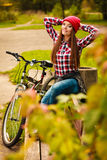 Girl relaxing in autumnal park with bicycle. Stock Photography