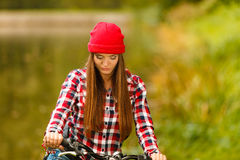 Girl relaxing in autumnal park with bicycle. Stock Images