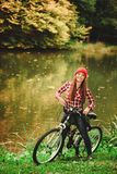 Girl relaxing in autumnal park with bicycle. Fall active lifestyle concept. Beauty young woman sporty casual girl relaxing in autumnal park with bicycle Royalty Free Stock Photo