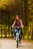 Girl relaxing in autumnal park with bicycle. Royalty Free Stock Photography