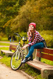 Girl relaxing in autumnal park with bicycle. Royalty Free Stock Images