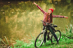 Girl relaxing in autumnal park with bicycle. Fall active lifestyle concept. Beauty young woman sporty casual girl relaxing in autumnal park with bicycle royalty free stock photos