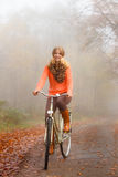 Girl relaxing in autumnal park with bicycle Stock Images