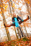 Girl relaxing in autumnal park with bicycle. Fall active lifestyle concept. Happy crazy woman girl vivid color shawl relaxing in autumn park riding bicycle with Stock Photography
